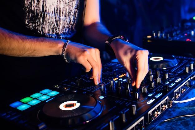 Mixer e cabina dj in discoteca con le mani del dj che mescolano musica e regolatori di controllo Foto Premium