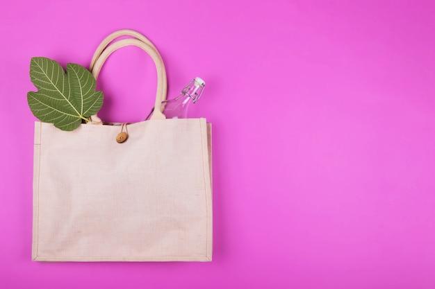 Mock up borsa di cotone con bottiglia di vetro e tovagliolo di bambù su rosa. stile eco minimalista. zero sprechi Foto Premium