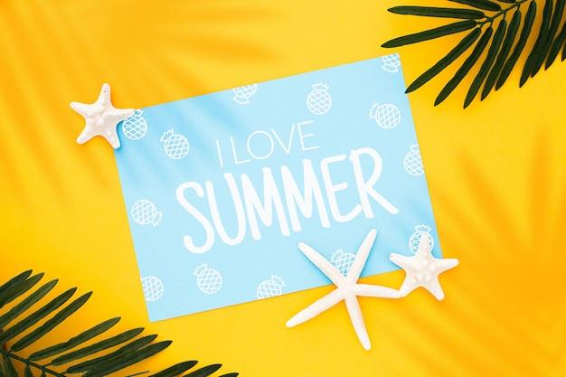 Mock up design su un'immagine di concetto di estate con foglie di palma e stelle marine su sfondo giallo Foto Gratuite