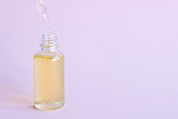 Mock-up in vetro per contagocce. pipetta osmetica sul rosa. Foto Premium