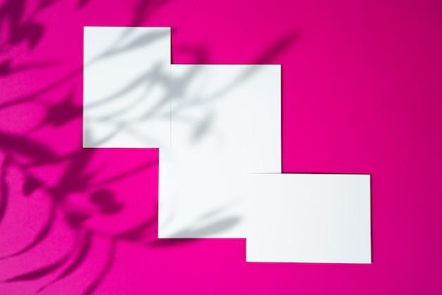 Mock-up pubblicitario. biglietti da visita bianco bianco su sfondo rosa brillante Foto Premium