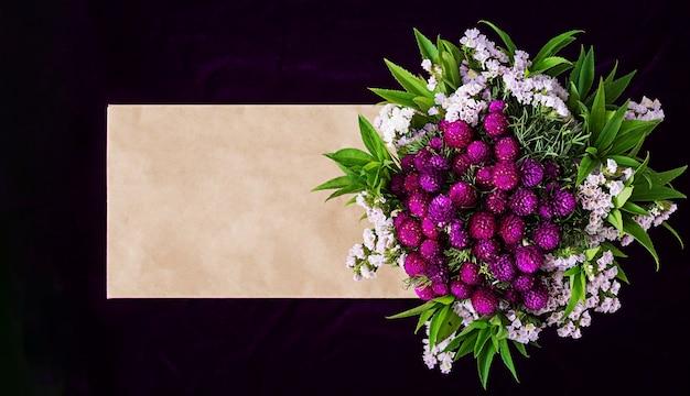 Mockup con busta di carta e fiori su sfondo scuro. Foto Premium
