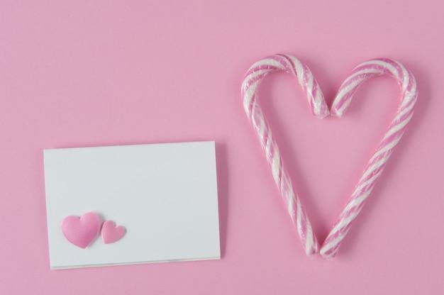 Mockup di carta di carta su sfondo rosa con cuori. due bastoncini di zucchero che fanno un cuore. vista dall'alto. disteso. confessione d'amore. Foto Premium