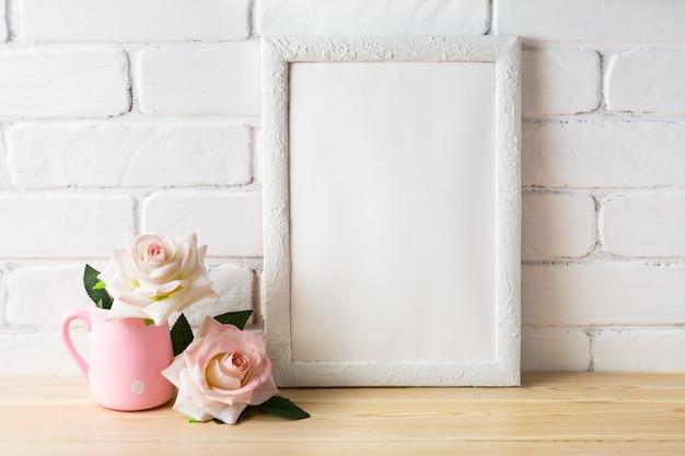 Mockup di cornice bianca con due rose rosa pallido Foto Premium