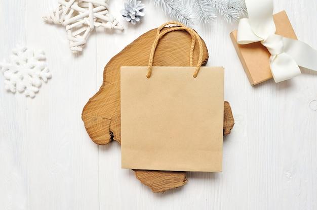 Mockup pacchetto artigianale di natale e regalo, flatlay su un fondo di legno bianco Foto Premium