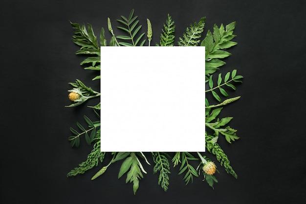 Mockup quadrato bianco nella cornice di foglie verdi Foto Premium