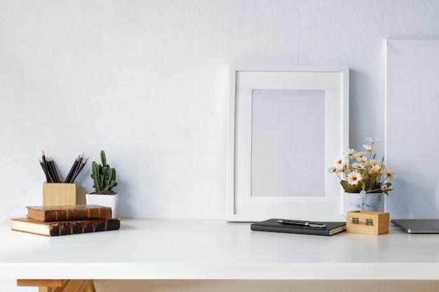 Mockup workspace vintage, fiori secchi, cancelleria per ufficio e cornice per poster Foto Premium