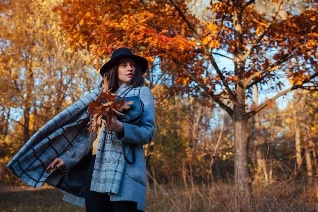 Moda autunno. giovane donna che cammina nel parco che indossa attrezzatura alla moda e che tiene borsa. abbigliamento e accessori Foto Premium