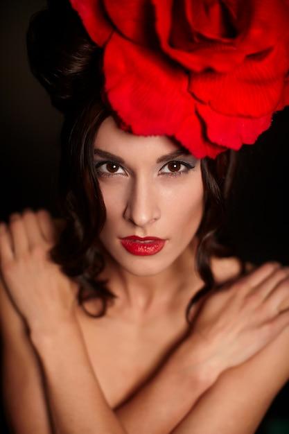 Moda bella donna con trucco luminoso e labbra rosse con grande rosa rossa sulla testa Foto Gratuite