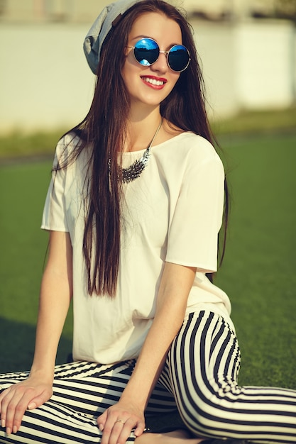 Moda elegante bella giovane donna bruna modello in estate casual abbigliamento casual in posa sullo sfondo di strada nel parco Foto Gratuite