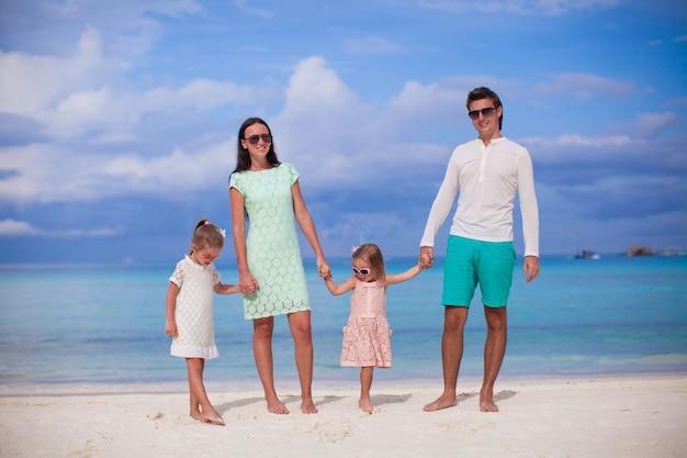 Moda famiglia di quattro persone a piedi al mare e godetevi le vacanze al mare Foto Premium