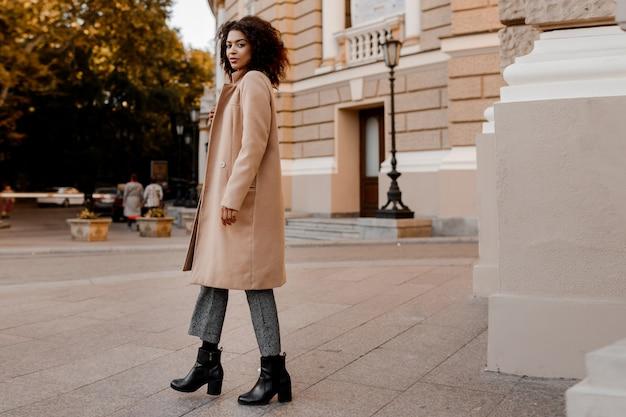 Moda immagine integrale di elegante donna di colore in elegante cappotto beige di lusso e maglione di velluto Foto Gratuite