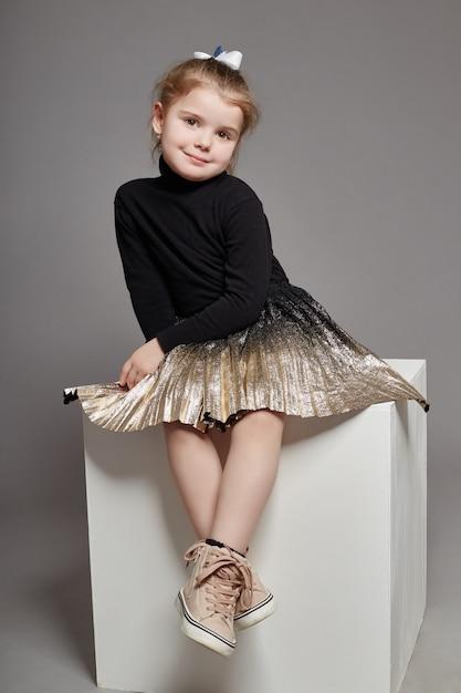 Moda ragazza capelli lunghi in abiti casual seduta Foto Premium