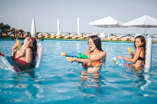 Modelli allegri e divertenti che giocano in piscina. tengono in mano pistole ad acqua e lo usano. due donne sono contro la terza. sorridono e ridono Foto Premium