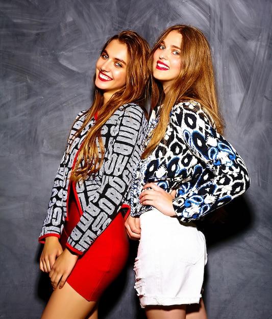 Modelli di belle giovani donne sorridenti sexy alla moda di fascino pazzo di stile di vita divertente in panno luminoso dei pantaloni a vita bassa di estate vicino alla parete grigia Foto Gratuite