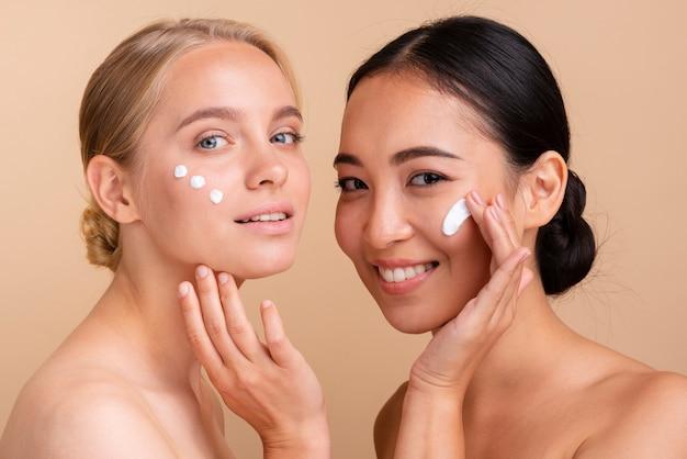 Modelli di close-up con crema per il viso in posa insieme Foto Gratuite