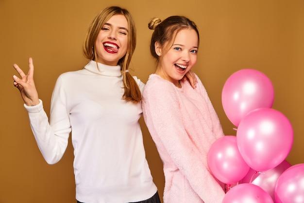 Modelli di donne con mongolfiere rosa sulla parete dorata Foto Gratuite