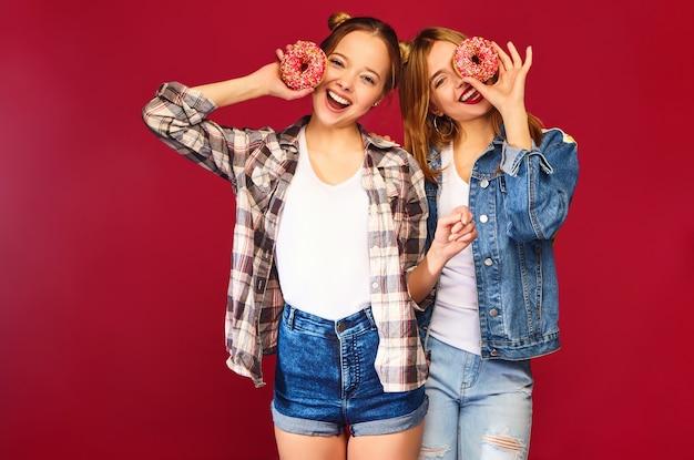 Modelli femminili in possesso di ciambelle rosa con spruzzi Foto Gratuite