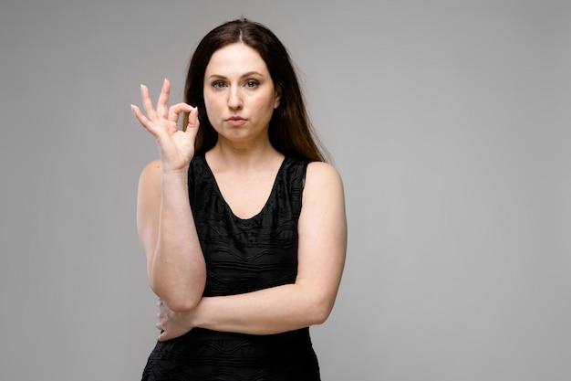 Modello abbastanza grande emozionale abbastanza serio che sta nello studio che mostra gesto giusto su fondo grigio Foto Premium
