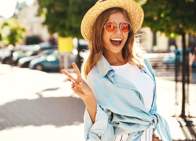 Modello biondo in abiti estivi in posa sulla strada che mostra il segno di pace Foto Gratuite