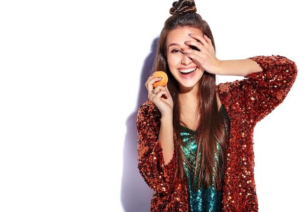 Modello castana sorridente caucasico bello della donna dei pantaloni a vita bassa in rivestimento alla moda di estate di riflessione shinny luminosa e vestito verde isolati. mangiare amaretto francese Foto Gratuite