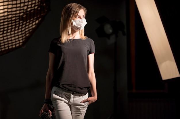Modello che indossa maschera medica in uno studio Foto Gratuite