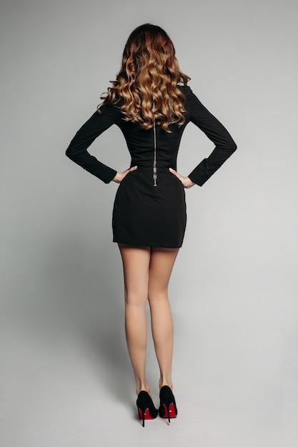 Modello con capelli mossi lucenti in mini abito nero e