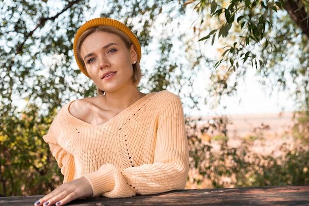 Modello con mano sul tavolo di legno Foto Gratuite