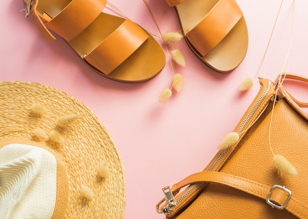 Modello con sandali in pelle marrone, cappello di paglia e borsa color sabbia con erba secca di coniglietto isolata su sfondo rosa. Foto Premium