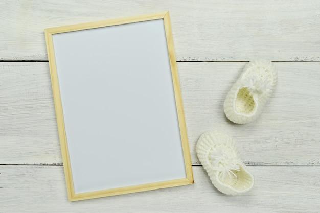 Modello. cornice vuota bianca con scarpe per bambini piccoli e vaso piccolo. Foto Premium