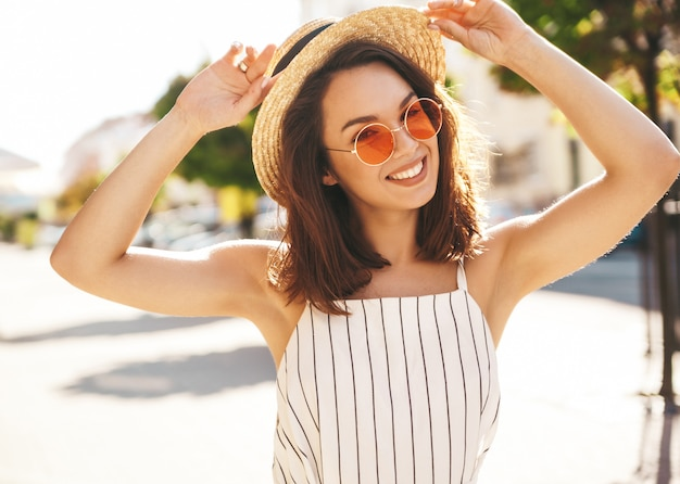 Modello del brunette in vestiti di estate che propongono sulla posa della via Foto Gratuite