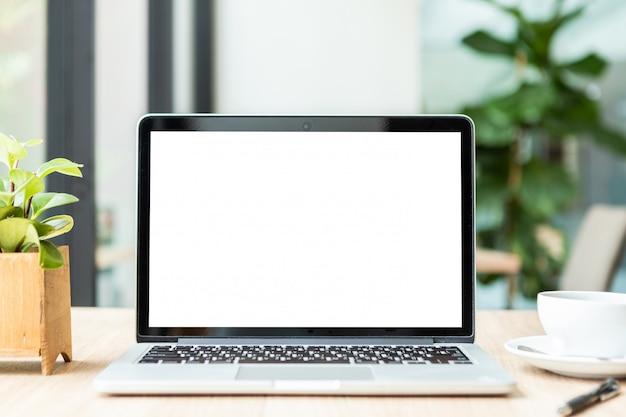Modello del computer portatile con lo schermo vuoto con la tazza di caffè sul tavolo della caffetteria Foto Premium