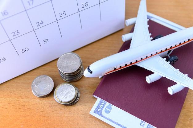 Modello dell'aeroplano con il calendario di carta sulla tavola di legno. pianificare il viaggio Foto Premium