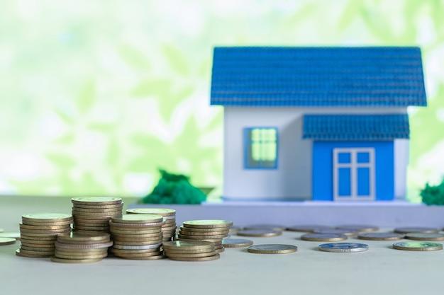 Modello della casa con le monete sulla tavola di legno Foto Gratuite