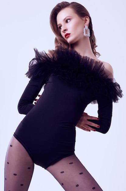 Modello della donna castana di fascino nell'ente nero con fatin isolato Foto Premium