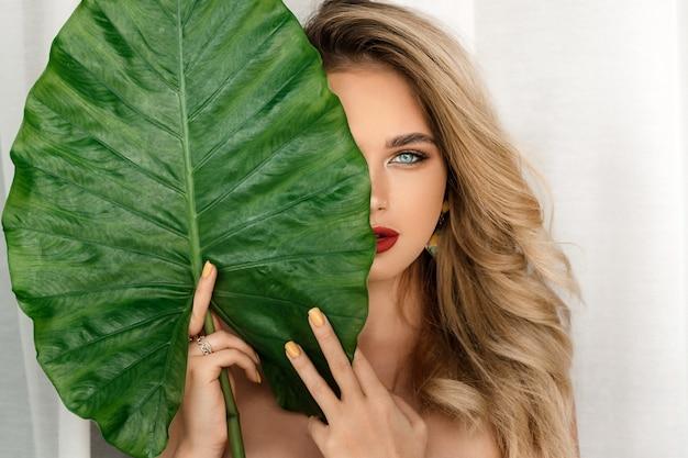 Modello della donna con trucco luminoso e pelle sana con la pianta verde della foglia Foto Premium