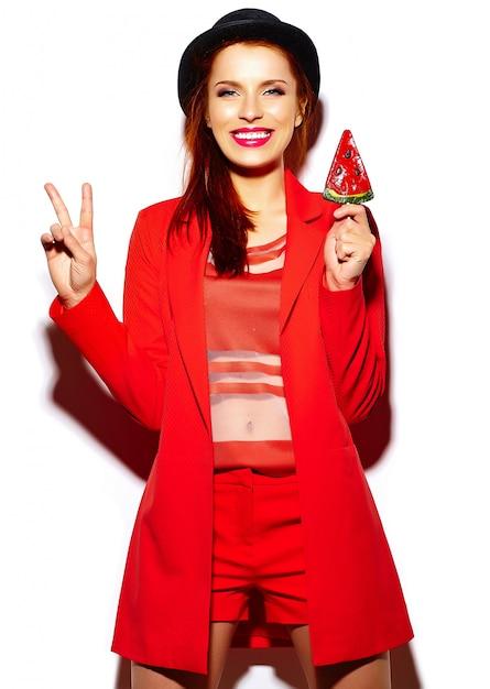 Modello di bella giovane donna divertente sorridente sexy alla moda di look.glamor di alta moda in panno casuale rosso intenso dei pantaloni a vita bassa di estate con la lecca-lecca dolce Foto Gratuite