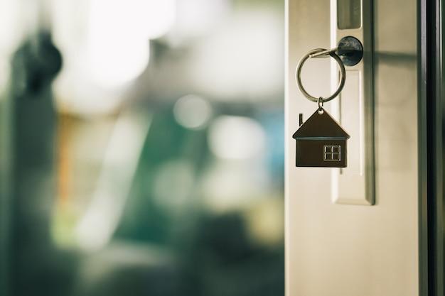 Modello di casa e la chiave nella porta di casa Foto Premium