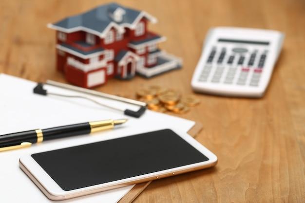 Modello di casa, smartphone, calcolatrice e monete d'oro sulla tavola di legno Foto Premium