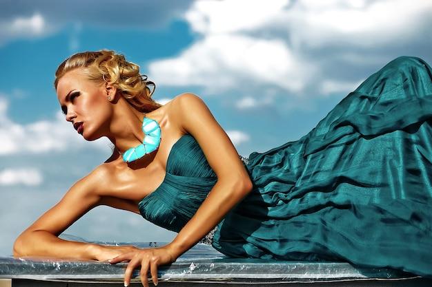 Modello di giovane donna bionda sexy in abito da sera in posa su sfondo blu cielo Foto Gratuite