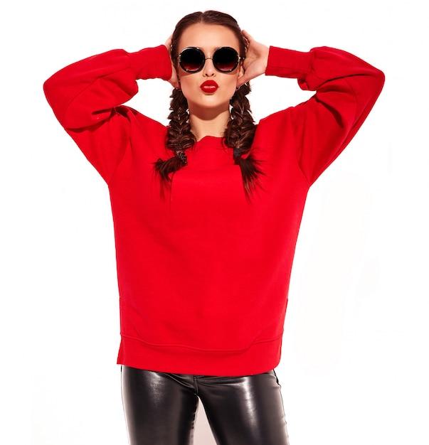 Modello di giovane donna sorridente felice con trucco luminoso e labbra colorate con due trecce e occhiali da sole in abiti rossi estate isolati. dando un bacio d'aria Foto Gratuite