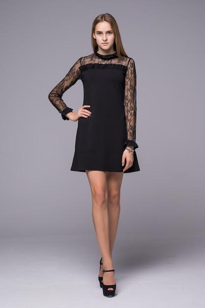 Modello di moda in vestito da modo che posa sul fondo grigio Foto Gratuite