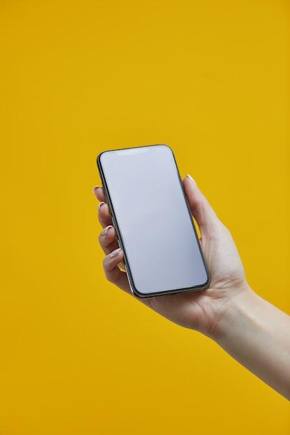 Modello di smartphone. mano femminile che tiene cellulare nero con con esposizione in bianco su fondo giallo Foto Premium