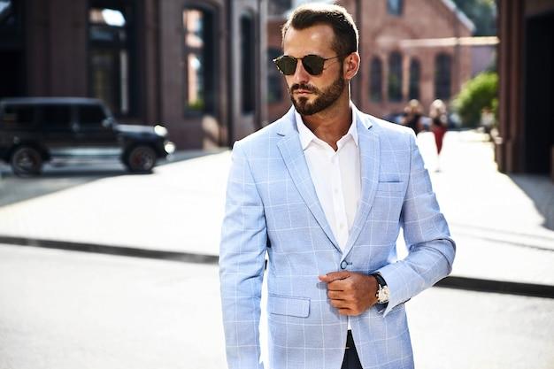 Modello di uomo d'affari moda bello vestito in elegante abito blu in posa sulla strada Foto Gratuite