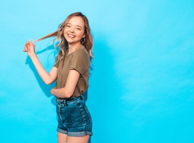 Modello divertente che posa vicino alla parete blu in studio. tocca i suoi capelli Foto Gratuite