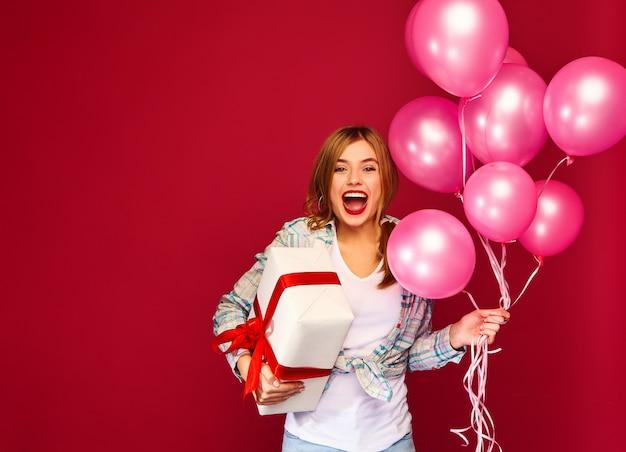 Modello donna che celebra e che tiene scatola con regalo presente e mongolfiere rosa Foto Gratuite