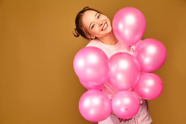 Modello donna con mongolfiere rosa sulla parete dorata Foto Gratuite
