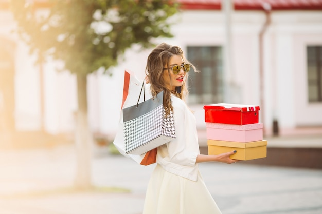 Modello felice nello sguardo bianco e negli occhiali da sole che tengono i sacchetti della spesa u Foto Premium
