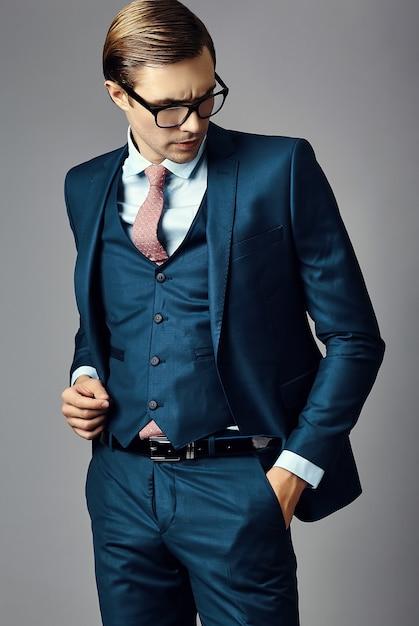 Modello maschio del giovane uomo d'affari bello elegante in un vestito e nei vetri alla moda, posanti nello studio Foto Gratuite