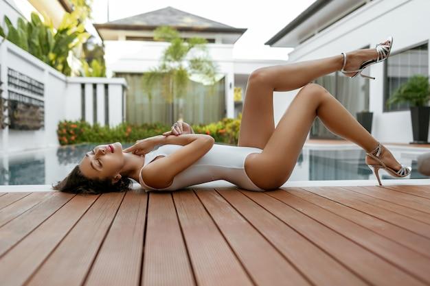 Modello sexy in costume da bagno intero bianco prende il sole vicino alla piscina. rilassati in una villa di lusso Foto Premium